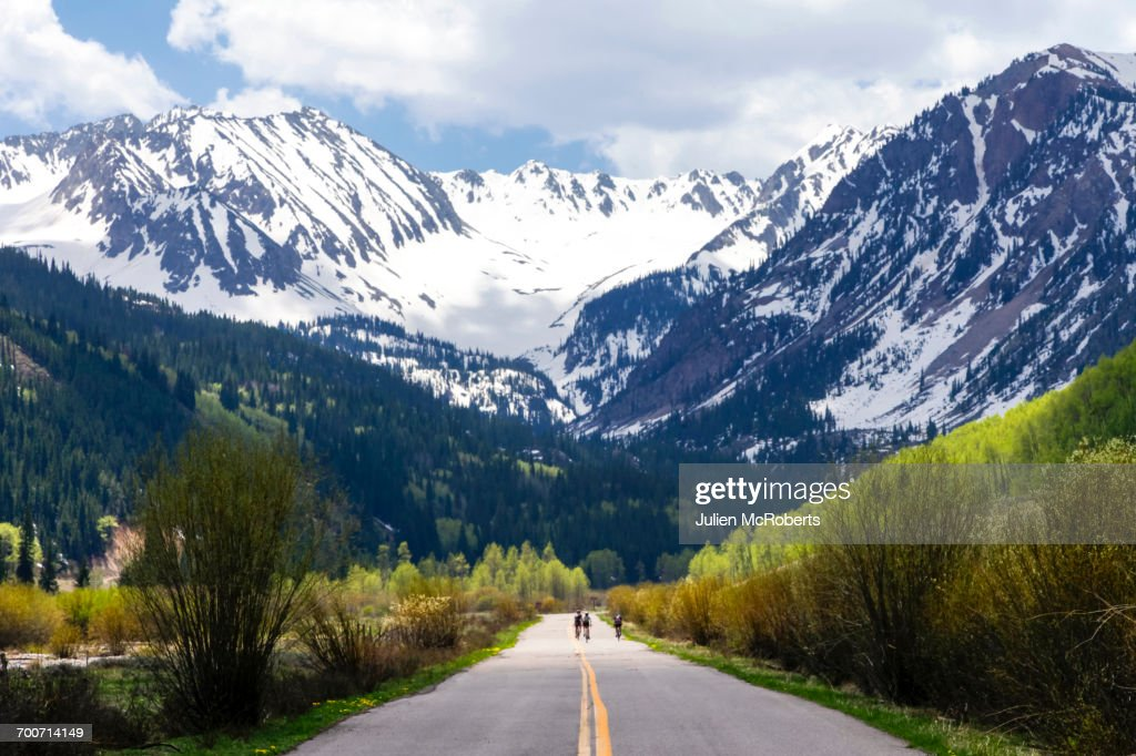 Distant people bicycling on road to mountain : Stock Photo
