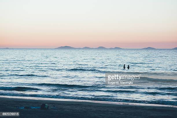 Distant people waist deep in ocean, Sorso, Sassari, Italy