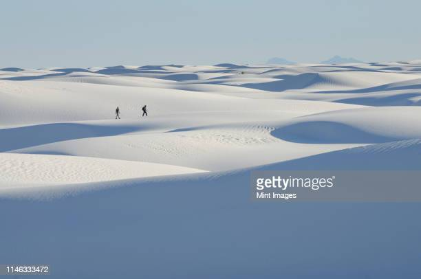 distant people walking on snowy landscape - new mexico stock pictures, royalty-free photos & images