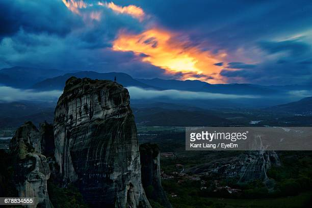 Distant Person On Top Of The Mountain Against Dramatic Sky