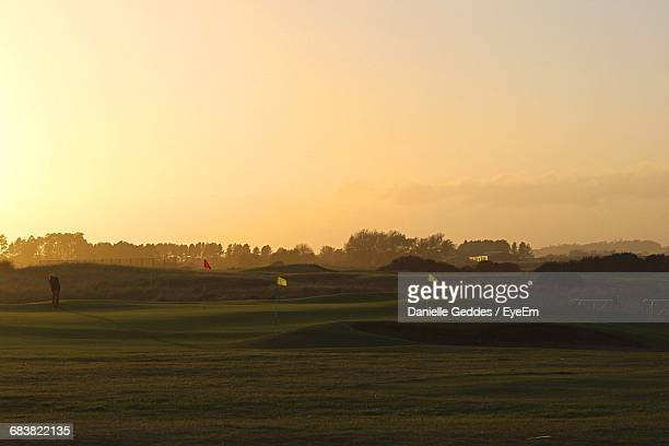 Distant Person Playing Golf At Sunset
