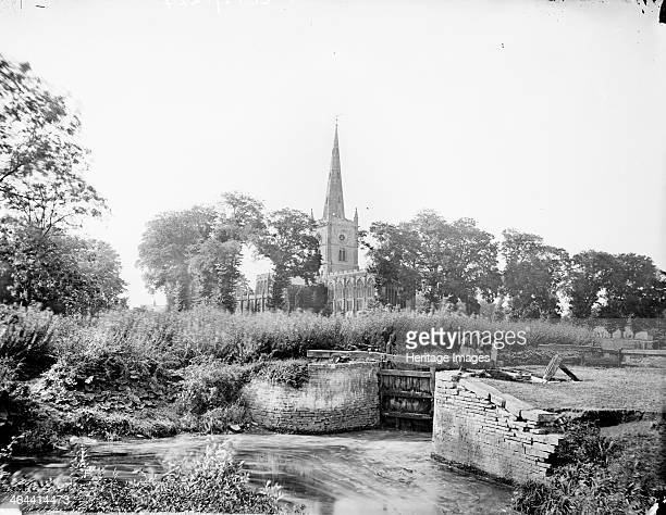 A distant prospect of Holy Trinity church Stratford upon Avon Warwickshire c1860c1922 In the foreground is a lock on the River Avon The church with...