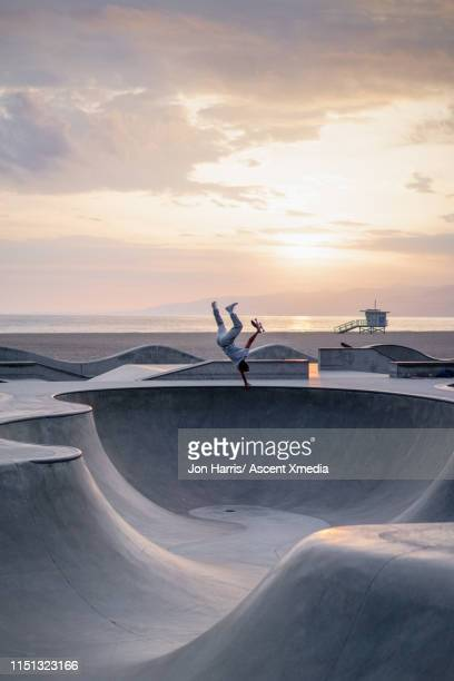 distant skateboarder performs stunts in park - achievement stock pictures, royalty-free photos & images