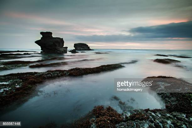 Distant Tanah Lot Temple seascape with dramatic cloud sky