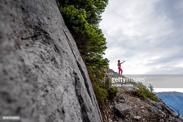 Distant trail runner takes picture from cliff edge