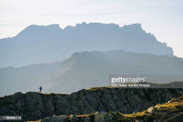 distant trail runner traverses mountain landscape - running stock pictures, royalty-free photos & images