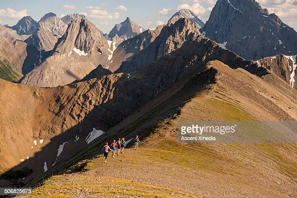 distant trail runners follow mountain ridge crest - following stock pictures, royalty-free photos & images