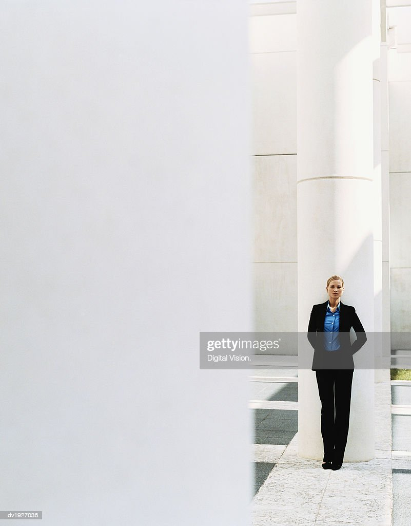 Distant View of a Businesswoman Leaning on a Pillar : Stock Photo