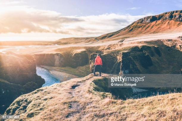 Distant view of a man with red coat admiring the view of the Fjadrargljufur canyon, Iceland.