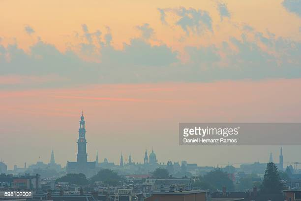 Distant view of Amsterdam Skyline with the church westerkerk in background at sunrise
