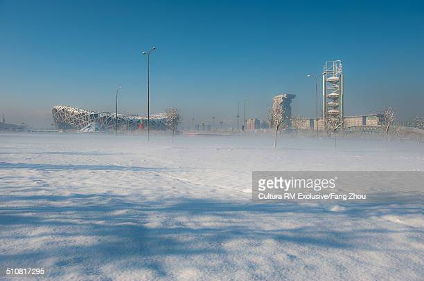 distant view of beijing national stadium (birds nest) and olympic park in snow, beijing, china - stadio olimpico nazionale foto e immagini stock
