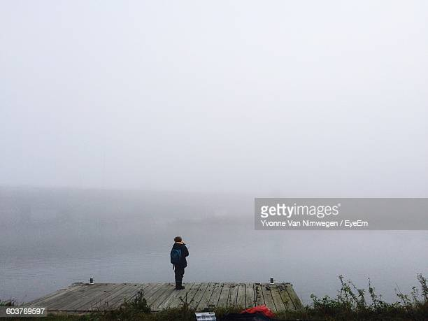 Distant View Of Boy Standing On Boardwalk By Lake During Foggy Weather