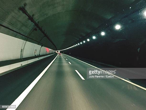 Distant View Of Car In Illuminated Tunnel