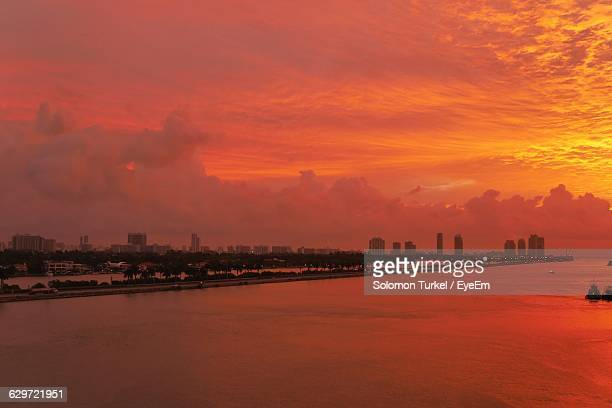 distant view of city by sea against cloudy sky during sunset - solomon turkel stock pictures, royalty-free photos & images
