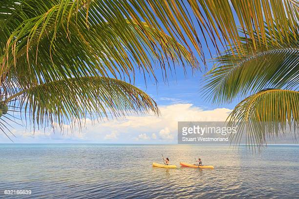 Distant view of couple sea kayaking, St. Georges Caye, Belize, Central America