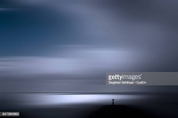 Distant View Of Cristo Rei Statue In Sea Against Sky At Dusk