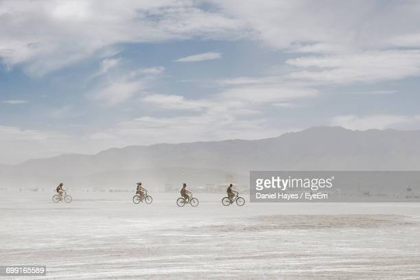 distant view of cyclists riding bicycles at desert against sky - dust storm stock pictures, royalty-free photos & images