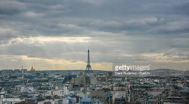 Distant View Of Eiffel Tower Amidst Cityscape Against Cloudy Sky
