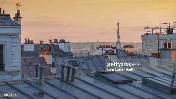 Distant View Of Eiffel Tower In City Against Sky During Sunset
