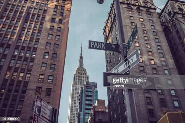 distant view of empire state building from park avenue. manhattan, new york - hotel plaza manhattan stock-fotos und bilder