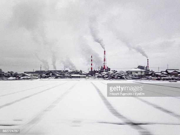 Distant View Of Factory On Snow Covered Field Against Sky