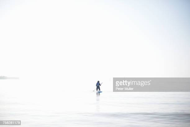 Distant view of female paddleboarder paddling out on misty sea