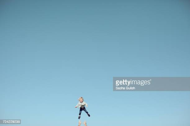 Distant view of female toddler thrown mid air against vast blue sky