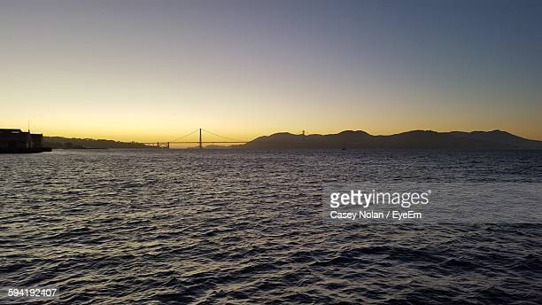 distant view of golden gate bridge over bay against sky - casey nolan stock pictures, royalty-free photos & images