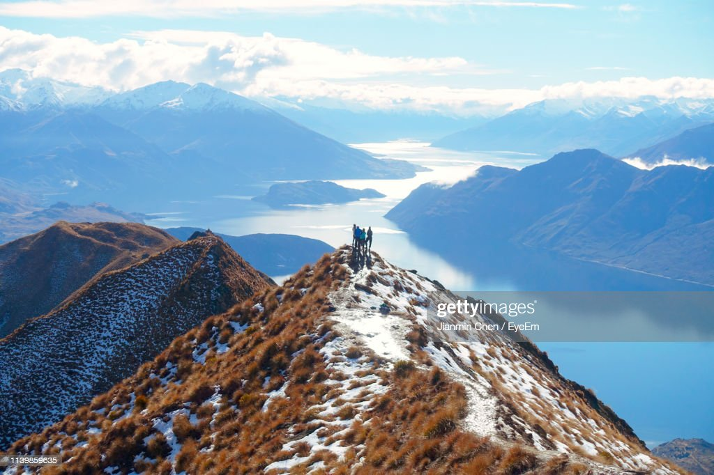 Distant View Of Hikers Standing On Cliff Against Lake During Winter : Stock Photo