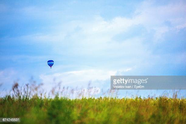 Distant View Of Hot Air Balloon Over Grassy Field Against Sky