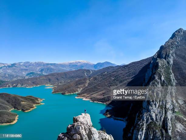 distant view of male hiker standing on cliff with lake in background against blue sky - tirana stock pictures, royalty-free photos & images