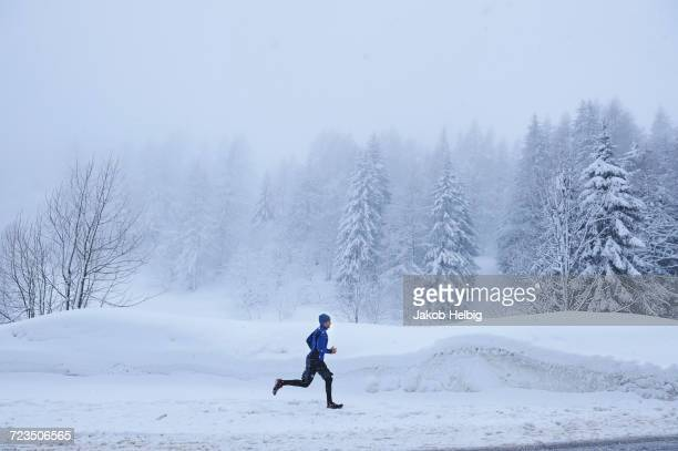 distant view of male runner running in deep snow, gstaad, switzerland - グスタード ストックフォトと画像
