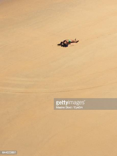 Distant View Of Man Lying On Sand