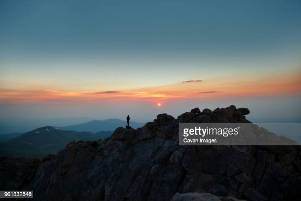 distant view of man standing on mountain during sunset - front range mountain range stock pictures, royalty-free photos & images
