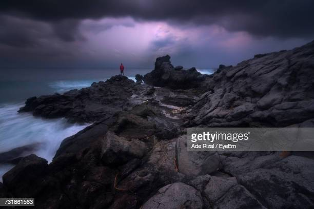 distant view of man standing on rock formation against cloudy sky at dusk - ade rizal stock photos and pictures