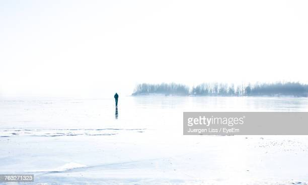 Distant View Of Man Walking On Snow Covered Field Against Clear Sky