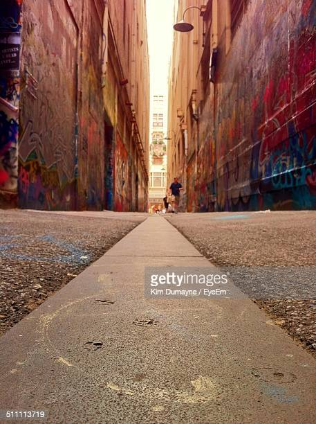 Distant view of man walking on street between buildings with graffiti walls