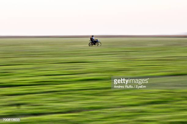 Distant View Of Men On Motorcycle At Grassy Field