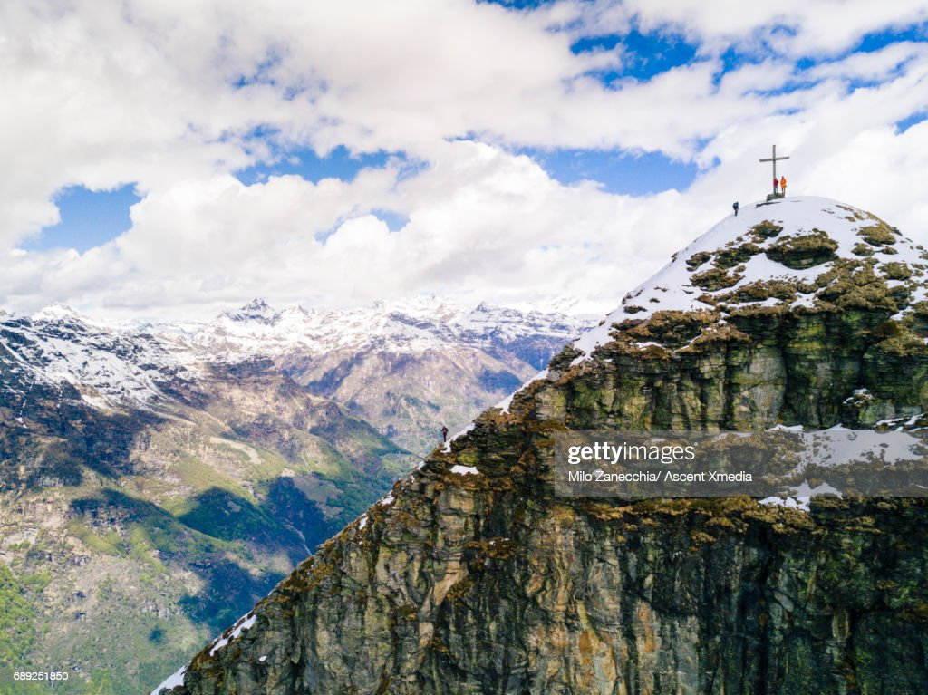 Distant view of mountaineers below mountain summit : Stock Photo