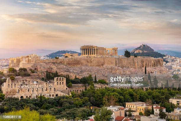 distant view of old ruins in city against cloudy sky during sunset - athens greece stock pictures, royalty-free photos & images