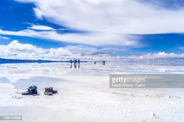 distant view of people on salt lake against cloudy sky - ウユニ塩湖 ストックフォトと画像