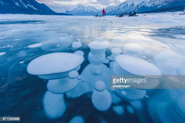 distant view of people playing on the frozen methane bubbles at abraham lake - see abraham lake stock-fotos und bilder