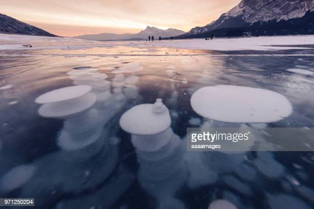 distant view of people playing on the frozen methane bubbles at Abraham Lake