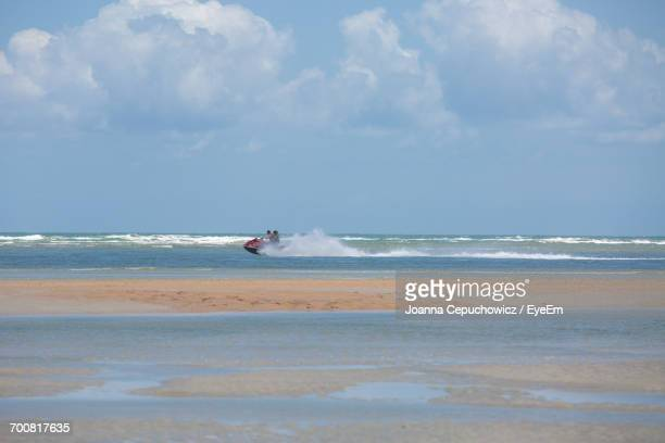 distant view of people riding jet boat on sea against cloudy sky - joanna jet stock pictures, royalty-free photos & images