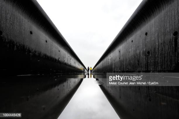distant view of people standing amidst buildings against sky - symmetry stock pictures, royalty-free photos & images