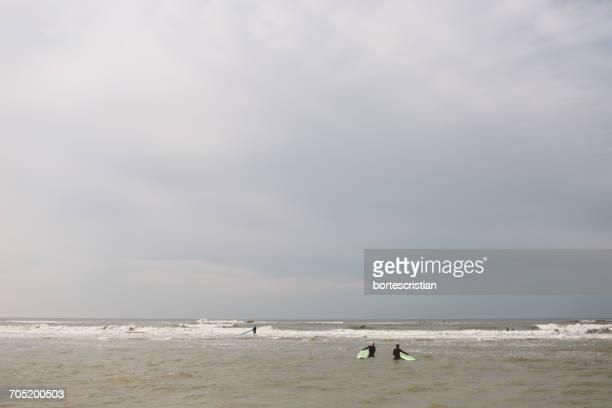 distant view of people with surfboards in sea against cloudy sky - bortes stockfoto's en -beelden