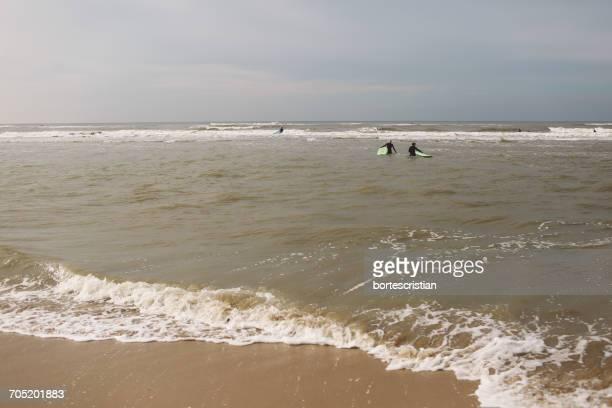 distant view of people with surfboards in sea - bortes stockfoto's en -beelden