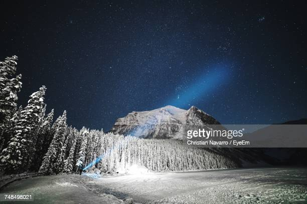 Distant View Of Person Showing Flashlight By Snowcapped Mountain Against Star Field At Night