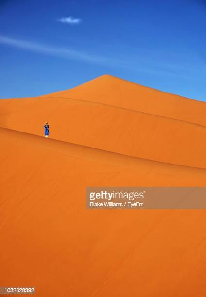 distant view of person standing at desert - merzouga stock pictures, royalty-free photos & images