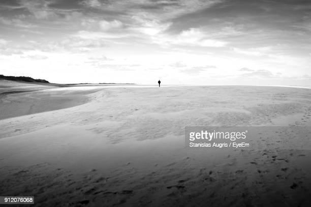 Distant View Of Person Standing On Sand Against Sky
